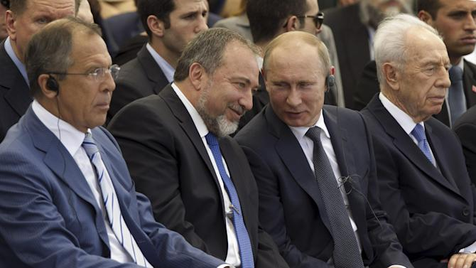 Russian President Vladimir Putin, third left, sits between Israel's Foreign Minister Avigdor Lieberman, second left, and Israeli President Shimon Peres during an inauguration ceremony of a memorial to Red Army veterans of World War II in Netanya, Israel, Monday June 25, 2012. The West's standoff with Iran over its nuclear program was expected to top the agenda on Monday as Russian President Vladimir Putin began a 24-hour visit to Israel. Sitting left is  Russian Foreign Minister Sergey Lavrov. (AP Photo/Jack Guez, Pool)