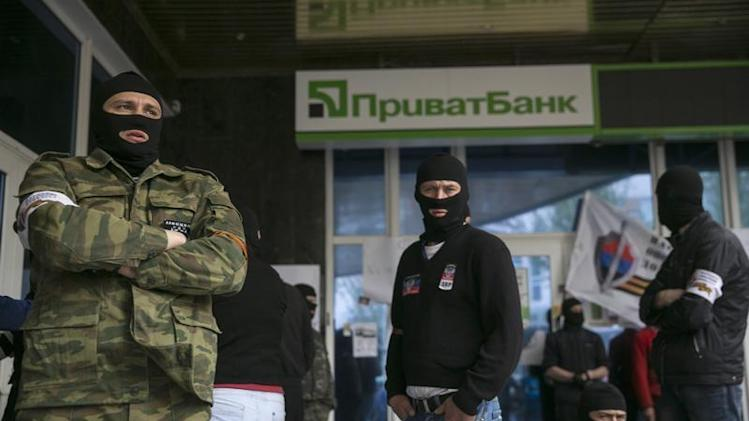 Masked pro-Russian activists stand outside a branch of Ukraine's Privatbank during a protest in Donetsk