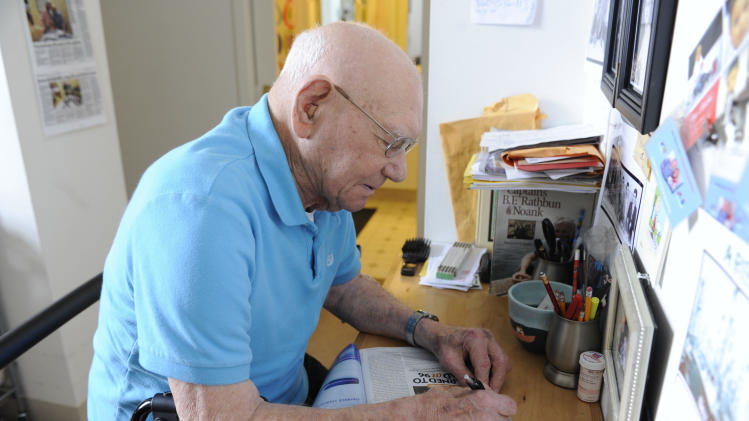 James Arruda Henry autographs a recent article in a magazine about him at his apartment in Mystic, Conn., Wednesday, March 28, 2012.  The 98-year-old retired lobsterman published his autobiographical essays after learning to read and write in his 90s. (AP Photo/Jessica Hill)