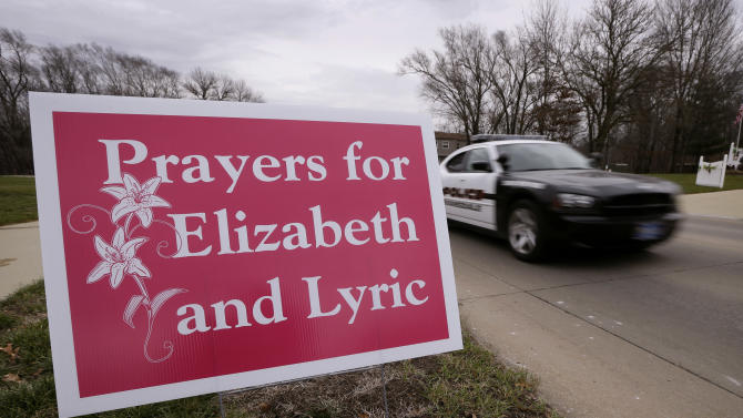 A police car passes a sign Thursday, Dec. 6, 2012, in Evansdale, Iowa, for cousins Lyric Cook, 10, and Elizabeth Collins, 8, who disappeared in July while riding their bikes at nearby Meyers Lake. Family members are waiting to hear whether the two bodies discovered by hunters on Wednesday are the two missing cousins. (AP Photo/Charlie Neibergall)