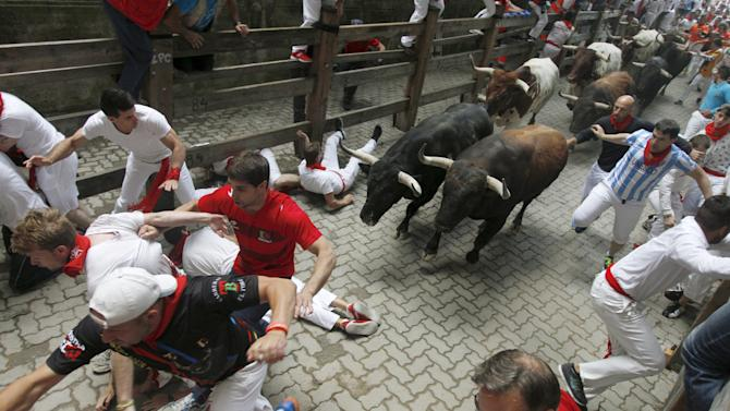 Runners fall in front of Tajo y la Reina fighting bulls at the entrance to the bullring during the second running of the bulls of the San Fermin festival in Pamplona