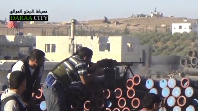 In this image taken from Wednesday, Sept. 25, 2013, video obtained from the Sham News Network, Syrian opposition fighters fire at government forces near Daraa customs in Daraa al-Balad, Syria. Russia offered on Thursday to provide troops to guard facilities where Syria's chemical weapons would be destroyed, as U.N. inspectors prepared to continue their probe on the use of such agents in the country's civil war. (AP Photo/Sham News Network via AP video)