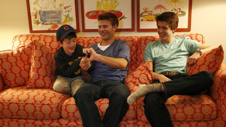 Peter Conkey, 6, left, laughs as he tries to keep his brother Harry Conkey, 17, center, from taking his iPod Touch as their brother Harry Conkey, 15, watches on Monday, March 11, 2013, in Wilmette, Ill. A new report from the Pew Internet & American Life Project says more teens are using smartphones as a main means of accessing the Internet -- moreso than adults. (AP Photo/Martha Irvine)
