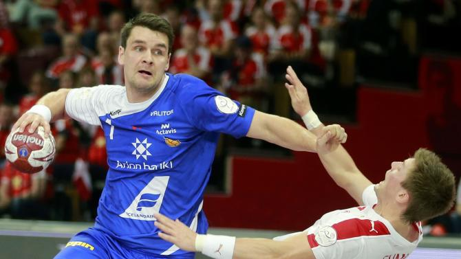 Atlason of Iceland is challenged by Hansen of Denmark during their round of 16 match of the 24th men's handball World Championship in Doha