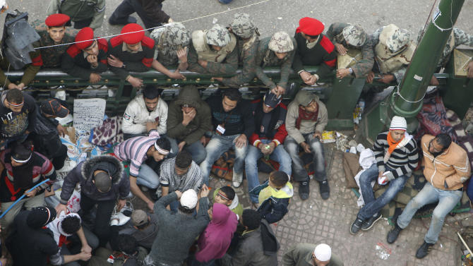 Military police and soldiers surround remaining protestors as they try to clear Tahir square in Cairo, Egypt, Monday Feb. 14, 2011. Egypt's military rulers dissolved parliament Sunday, suspending the constitution and promising elections in moves cautiously welcomed by pro-democracy protesters.(AP Photo/Hussein Malla)