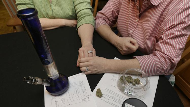 Wearing their wedding rings, Kimberly Bliss, left, and her wife Kim Ridgway, right, pose for a photo, Wednesday, Feb. 27, 2013 at their home in Lacey, Wash. On the table in front of them is medical marijuana and a water pipe that Ridgway uses to treat arthritis and severe anxiety. The couple got married on Dec. 9, 2012, thanks to the state's new gay marriage law, and now they are trying to take advantage of another measure voters approved in November by planning to open a state-licensed marijuana store. (AP Photo/Ted S. Warren)