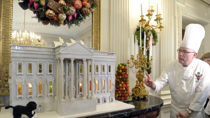 White House Pastry Chef Bill Yosses explains his design for the nearly 300-pound gingerbread house of the White House, on display in the State Dining Room of the White House in Washington, Wednesday, Nov. 28, 2012. The house features Bo, the Obama family dog, left,  a vegetable garden and views inside the White House. The theme for the White House Christmas 2012 is Joy to All. The White House gingerbread house has been a tradition since the 1960s. (AP Photo/Susan Walsh)