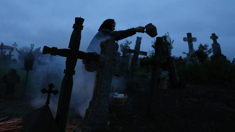 Woman burns incense in front of the graves of her relatives at a cemetery in the village of Copaciu