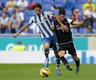 Malaga's Isco (L) clashes with Espanyol's Raul Rodriguez during their Spanish La Liga match at the Cornella-El Prat stadium in Cornella. The match ended in a 0-0 draw