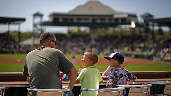 John Shirk, left, of Bradenton, Fla., sits on the outfield deck with his sons Baron, 4, center, and Oakley, 6, at McKechnie Field during the Pittsburgh Pirates intrasquad spring training baseball game inn Bradenton, Fla., Monday, March 2, 2015. (AP Photo/Gene J. Puskar)