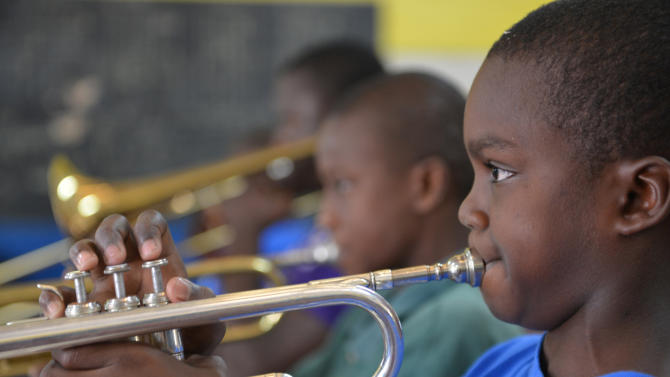 In this Feb. 17, 2014 photo, 11-year-old Tyrone Muirhead, right, is plays the trumpet with the band at the Alpha Boys' School, a residential vocational school in Kingston, Jamaica. The school has been a cornerstone of Jamaica's prolific musical culture for over a century, producing numerous musicians who have taken the homegrown musical genres of ska, rocksteady and reggae to the world. But despite its outsized role in developing Jamaica's world-famous music, the school is increasingly squeezed between rising costs and shrinking state support, barely scraping by on the $60 weekly the government provides per student. (AP Photo/David McFadden)