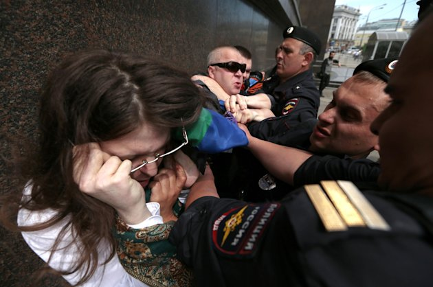 "Police detain a gay rights supporter, left, and an opponent, right, who scuffle during an unsanctioned gay rally near the City Hall in Moscow, Saturday, May 25, 2013. The Kremlin initiated a bill banning ""propaganda of homosexuality"" and routinely banned gay rallies and parade. Russian police say they detained at least 30 gay rights campaigners and their opponents at an unsanctioned rally in Moscow. (AP Photo/Ivan Sekretarev)"