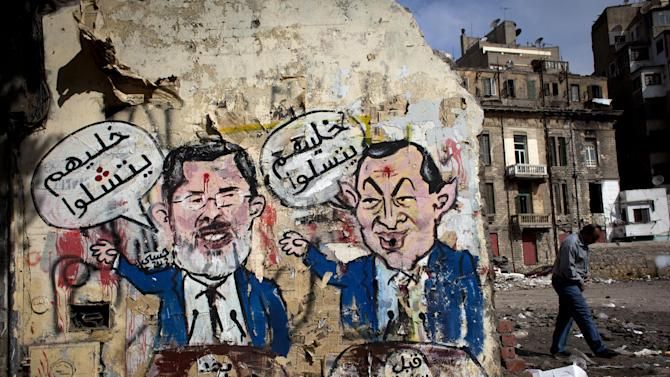 """An Egyptian man walks by a mural depicting ousted president Hosni Mubarak, right, and Egyptian President Mohammed Morsi, left, with Arabic that reads """"before the revolution, let them be amused, after the revolution, let them be paralyzed,"""" on a wall in Tahrir Square, Cairo, Egypt, Tuesday, Feb. 19, 2013. An ultraconservative Islamist adviser to Egypt's president resigned yesterday in solidarity with a fellow aide who was fired amid allegations of abuse of office. (AP Photo/Nasser Nasser)"""