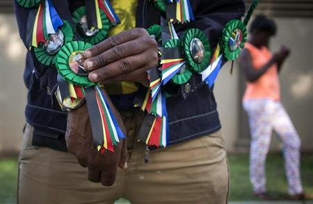 A man sells pins with the image of Nelson Mandela outside the Mandela house in the Houghton Estates neighborhood of Johannesburg