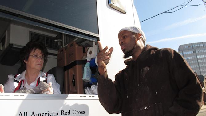In this Monday, Nov. 12, 2012 photo, Red Cross volunteer Ellen Foreman, left, speaks with Ralph Royster, right, who was seeking a hot meal in Atlantic City N.J., two weeks after Superstorm Sandy devastated the Jersey shore. Though hard-hit by the storm, many of Atlantic City's poorest residents are enduring its hardships with quiet acceptance and gratitude for the help being offered to them. (AP Photo/Wayne Parry)