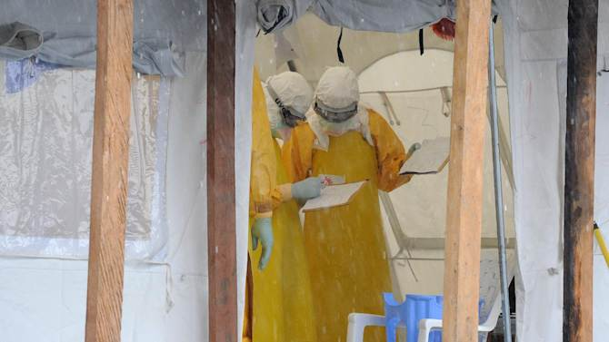Health care workers, wearing protective suits, work at the Elwa hospital in Monrovia on August 30, 2014