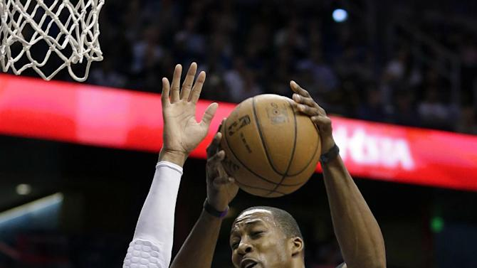 Los Angeles Lakers' Dwight Howard (12) makes a shot over Orlando Magic's Tobias Harris, left, during the first half of an NBA basketball game, Tuesday, March 12, 2013, in Orlando, Fla. (AP Photo/John Raoux)