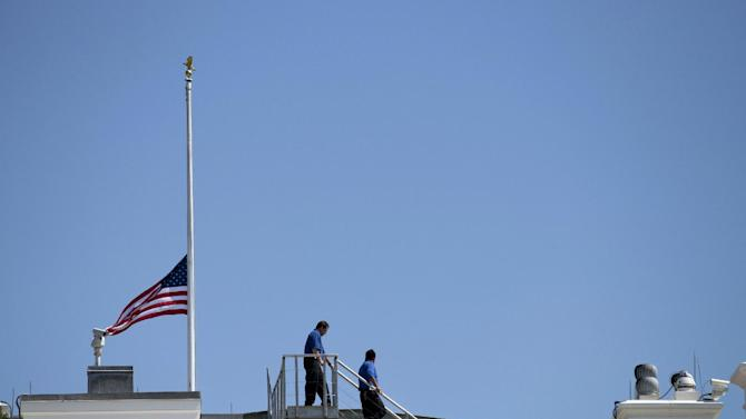 White House workers walk on the roof of the White House after lowering the flag to half staff for the death of U.S. ambassador to Libya Christopher Stevens, Wednesday, Sept. 12, 2012 in Washington.  (AP Photo/Evan Vucci)