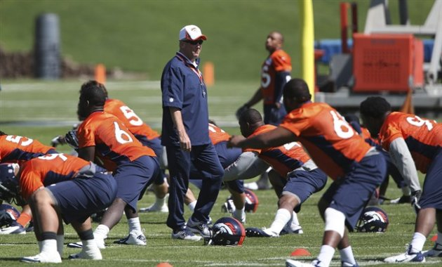 Denver Broncos head coach John Fox, center, watches as defensive players stretch during off season training camp at the NFL football team's training facility in Englewood, Colo., on Monday, May 10, 20