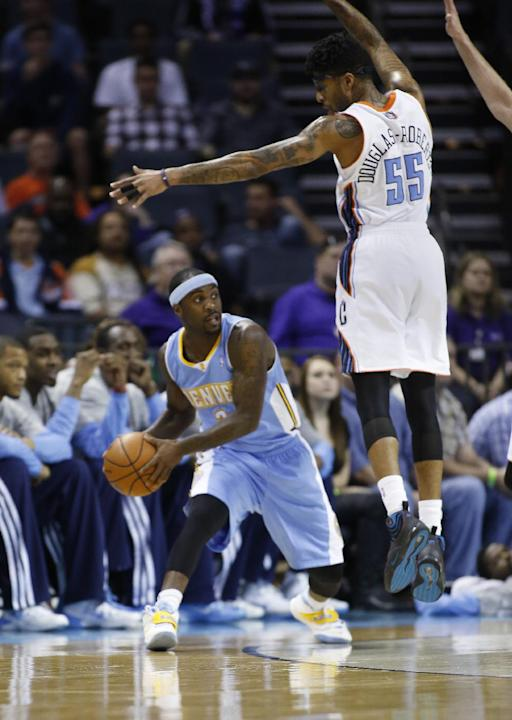 Denver Nuggets guard Ty Lawson, left, looks to pass around Charlotte Bobcats guard Chris Douglas-Roberts during the first half of an NBA basketball game in Charlotte, N.C., Monday, March 10, 2014