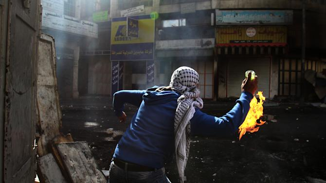 A Palestinian protester throws a Molotov cocktail towards Israeli soldiers, not pictured, during clashes in the West Bank city of Hebron, Wednesday, April 3, 2013. Palestinian prisoners have been rioting and hunger striking since a 64-year-old prisoner died of throat cancer on Tuesday. The Palestinians have blamed Israel for the man's death, saying he was not given proper medical care. The prisoner, Maysara Abu Hamdiyeh, had been serving a life sentence for his role in a foiled attempt to bomb a busy cafe in Jerusalem in 2002. (AP Photo/Nasser Shiyoukhi)