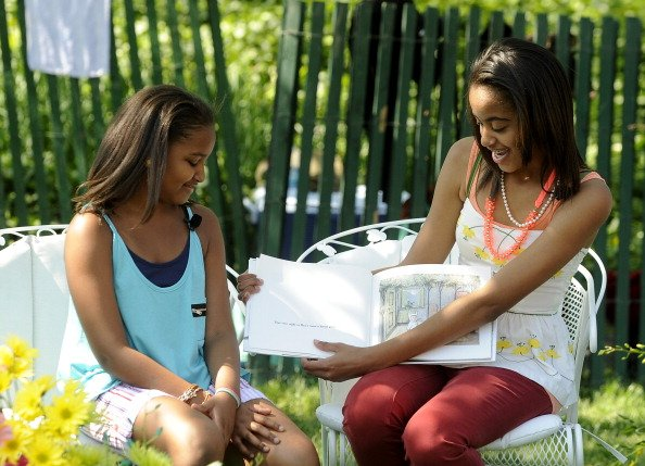 Sasha Obama and Malia Obama read to children during the White House Easter Egg Roll on the South Lawn of the White House on April 25, 2011 in Washington, DC. About 30,000 people are expected to attend
