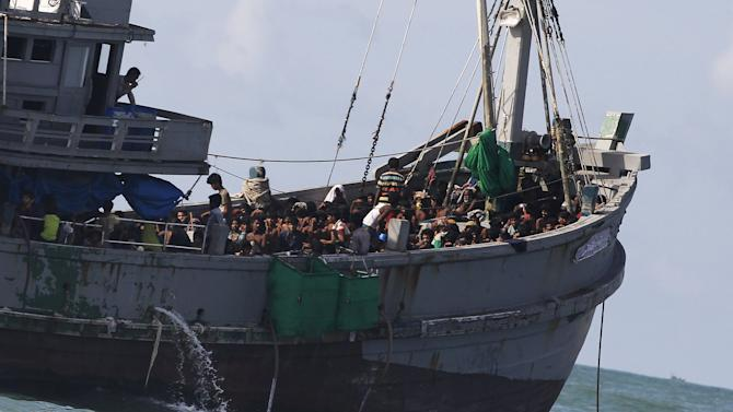 A Myanmar military officer speaks on the radio from a boat packed with migrants off Leik Island in the Andaman Sea