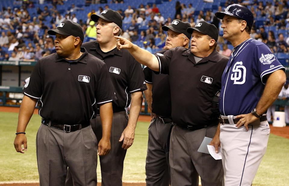 Umpires, from left, Adrian Johnson, Bill Welke, Brian O'Nora and Fieldin Culbreth meet with San Diego Padres third base coach Glenn Hoffman before an interleague baseball game against the Tampa Bay Rays, Friday, May 10, 2013, in St. Petersburg, Fla. (AP Photo/Mike Carlson)