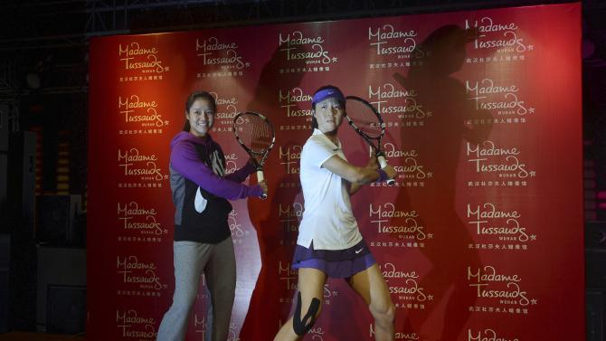 File photo of China's tennis player Li Na posing next to a wax statue of herself during the statue's unveiling ceremony at Madame Tussauds Wuhan