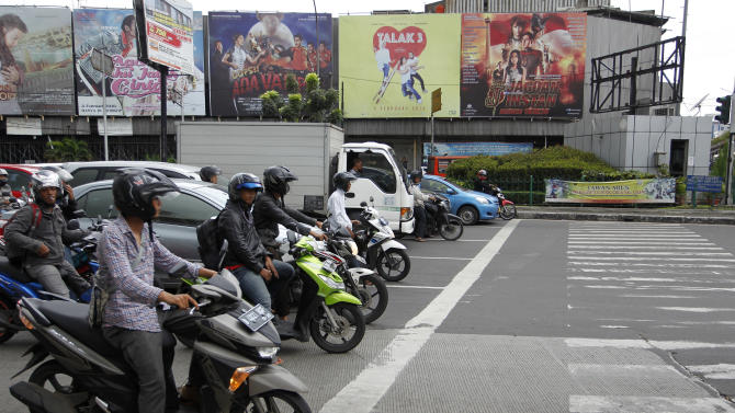 Motorcyclists wait at an intersection near posters for locally made films on a street in Jakarta