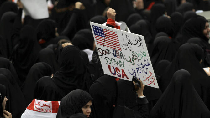 "In this photo taken May 18, 2012, Bahraini anti-government protesters participating in mass march along a northern highway outside Manama, Bahrain, carry a sign reading in Arabic, ""Death to America, the enemy of the nations and the creator of wars. Death to America."" During one of the nightly clashes with Bahrain's security forces, a new chant broke out among opposition protesters: ""The U.S. is the big devil."" A few days later, pro-government marchers also waved their fists against Washington. Both sides in the Bahrain meltdown are finding a shared target in the United States. (AP Photo/Hasan Jamali)"