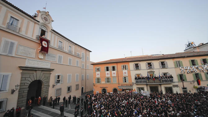 Pope Benedict XVI waves from the balcony window of the Pontifical summer residence in Castel Gandolfo, some 35 kilometers south of Rome, to a cheering crowd gathered to see him the day he ends his pontificate, Thursday, Feb. 28, 2013. (AP Photo/Alessandra Tarantino)