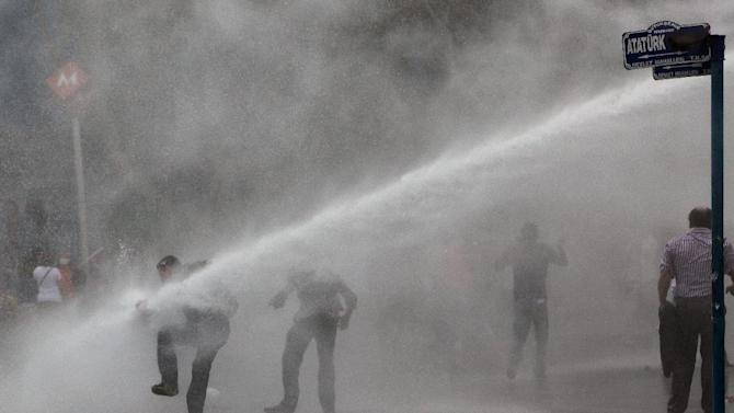 Turkish riot police spray water cannon at demonstrators who remained defiant after authorities evicted activists from an Istanbul park, making clear they are taking a hardline against attempts to rekindle protests that have shaken the country, in city's main Kizilay Square in Ankara, Turkey, Sunday, June 16, 2013.(AP Photo/Burhan Ozbilici)