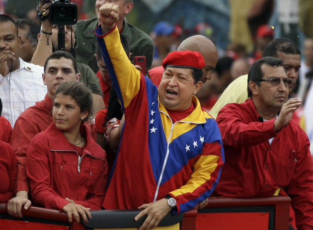 Venezuela's President Hugo Chavez waves to the crowd while riding atop a truck upon his arrival to the elections office in Caracas, Venezuela, Monday, June 11, 2012. Chavez rallied thousands of his supporters wearing his signature red beret and blowing kisses to the crowd as he formalized his presidential candidacy and launched his re-election bid.Second from left is Chavez's younger daugther Rosines and at right his brother Adan.(AP Photo/Ariana Cubillos)
