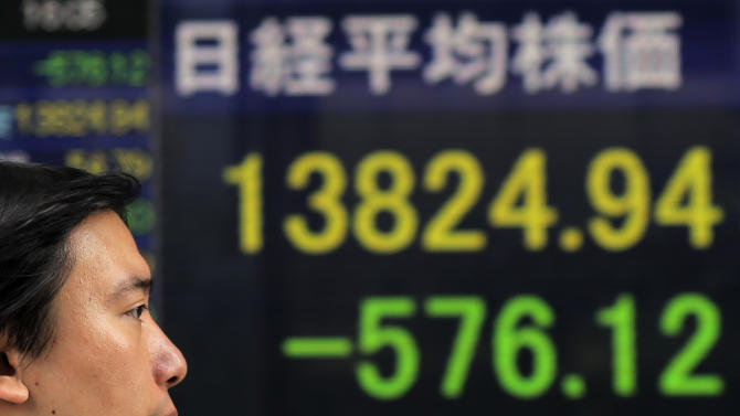 A man walks by an electronic stock board of a securities firm indicating a sharp drop of 576.12 points, or 4.00 percent, to 13,824.94 in Tokyo Wednesday, Aug. 7, 2013. Asian stock markets fell Wednesday, led by a tumble in Tokyo's benchmark, as expectations mounted that the U.S. central bank will begin to phase out its monetary stimulus next month. (AP Photo/Itsuo Inouye)