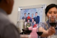 A family photo is seen on the wall at Li Na's home in Beijing, on May 12, 2013. With two cars, foreign holidays and a cook for their apartment, Li's family epitomises the new middle class created by China's decades of rapid economic growth