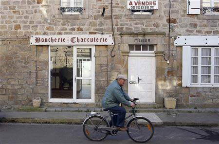 A man rides his bicycle in a street in Sousceyrac, a rural town in south-central France