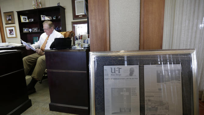 """In this photo taken Oct. 10, 2012, John Lynch, CEO of the U-T San Diego newspaper, reads mail in his office in San Diego. Lynch and his partner Douglas Manchester gave their 143-year-old newspaper a new slogan — """"The World's Greatest Country & America's Finest City"""" — ran a front-page editorial that declared their plan to reshape the city's downtown waterfront their highest priority, and forecast doom if President Barack Obama wins re-election. (AP Photo/Gregory Bull)"""