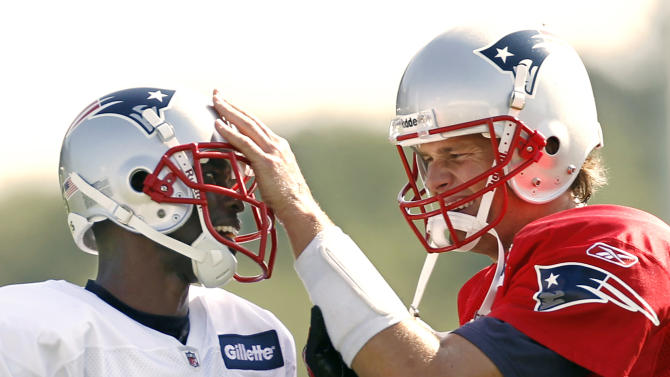 New England Patriots quarterback Tom Brady, right, fools around with new teammate Chad Ochocinco during training camp practice in Foxborough, Mass. Saturday, July 30, 2011. (AP Photo/Winslow Townson)