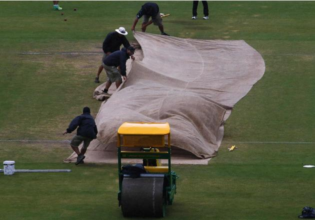 Grounds workers cover the pitch as the start of the match was delayed due to rain during the fifth day's play in the second Ashes cricket test between England and Australia at the Adelaide Oval