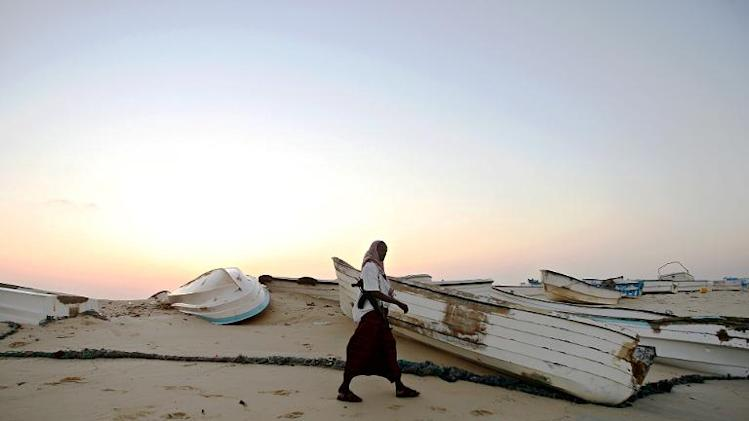 An armed pirate walking past skiffs, used to raid ships on the high-seas, at the coastal town of Hobyo, on November 10, 2009
