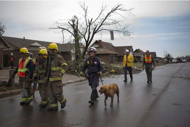 Rescue workers use a canine while searching house-to-house for survivors in a neighborhood left devastated by a tornado in Moore, Oklahoma