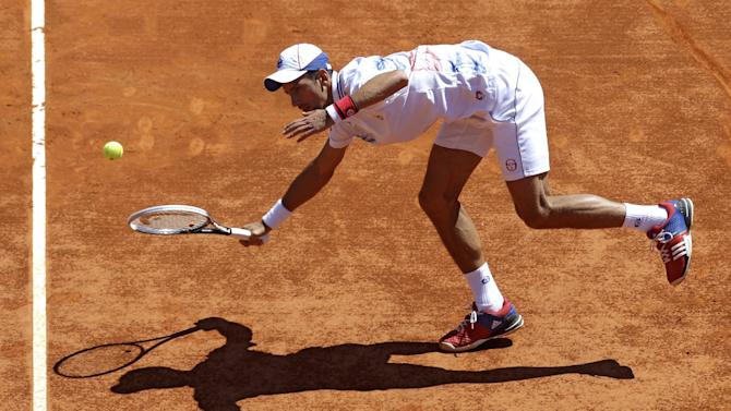 Novak Djokovic of Serbia plays a return shot to Tomas Berdych of Czech Republic during their semifinal match of the Monte Carlo Tennis Masters tournament in Monaco, Saturday, April 21, 2012. (AP Photo/Lionel Cironneau)