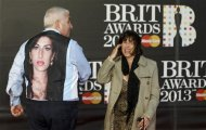 Mitch and Janis Winehouse, the father and mother of the late singer Amy Winehouse, laugh as they arrive for the BRIT Awards at the O2 Arena in London February 20, 2013. REUTERS/Luke Macgregor