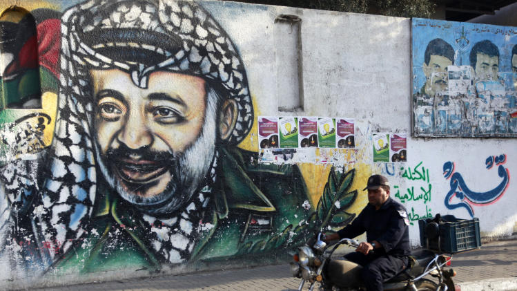 A Palestinian officer rides a motorcycle passes by a mural depicting the late Palestinian leader Yasser Arafat, in Gaza City, Monday, Nov. 11, 2013. Arafat died Nov. 11, 2004 at a French military hospital, a month after falling ill at his West Bank headquarters. (AP Photo/Hatem Moussa)