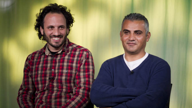 "In this Tues., Feb. 5, 2013 photo, documentary film Co-directors, Israeli, Guy Davidi, left, and Palestinian, Emad Burnat, pose for a photo after an interview in Los Angeles. Their 2011 documentary film, ""5 Broken Cameras,"" is nominated for an Oscar in the best Documentary Feature category.  (AP Photo/Damian Dovarganes)"