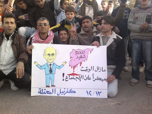 Demonstrators against Syria's President al-Assad hold a poster with a picture representing Arab League Secretary General Elaraby in Kafranbel near Adlb