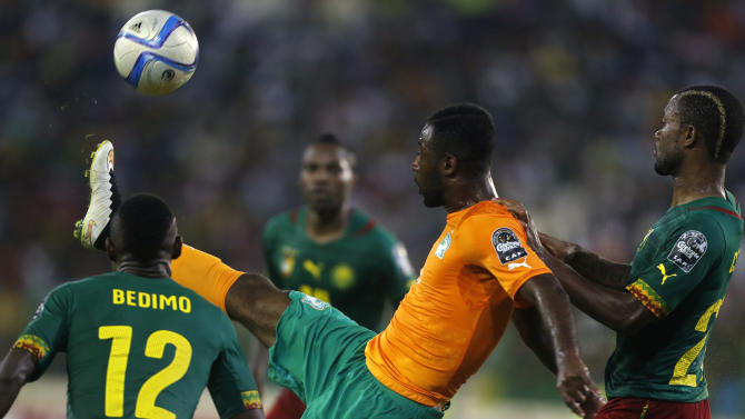 Tallo of Ivory Coast fights for the ball with Chedjou and Bedimo of Cameroon during their Group D soccer match of the 2015 African Cup of Nations in Malabo