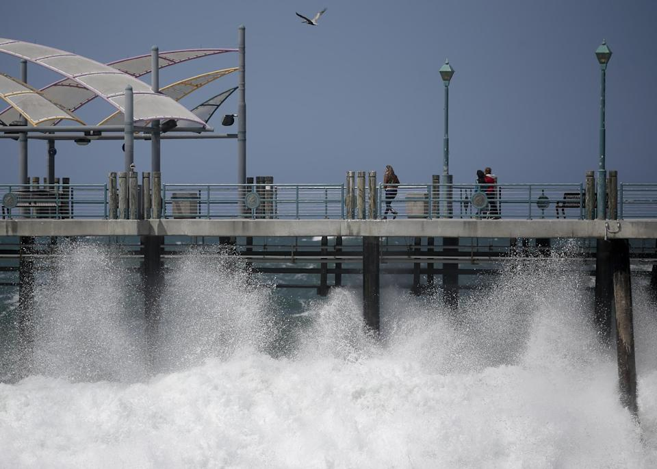 Waves hit the Redondo Beach Pier in Redondo Beach, Calif., Monday, April 8, 2013. Strong winds have begun raking parts of Southern California. The National Weather Service says the gusty northwest-to-north winds will become widespread across the region Monday and continue into the night.(AP Photo/Jae C. Hong)