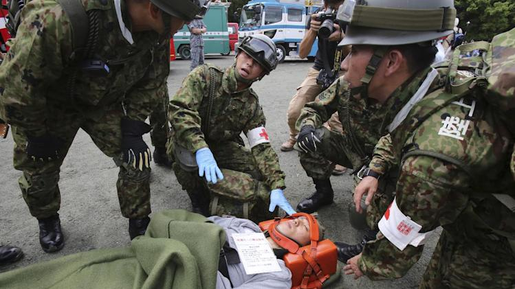 Members of Japan Ground Self Defense Forces attend an injured person during an annual disaster drill in Tokyo, Saturday, Aug. 30, 2014. The purpose of the drill was to prepare emergency responders and local citizens on how they deal with a real disaster situation if occurs in the metropolitan area ahead of the Sept. 1 anniversary of the great Kanto earthquake in 1923. Nearly 10,000 people of citizens, military, fire and police departments took part in the drill. (AP Photo/Koji Sasahara)